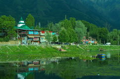 Beautiful scene near Dal lake in Kashmir-2. A beautiful scene of a locality situated nearby lush green trees besides a lake in Kashmir Stock Images