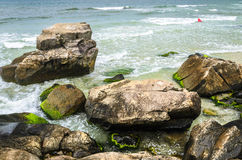 Beautiful scene with stones with green moss on the seashore. Sea water passing between them, some small waves and people swimming in the background Royalty Free Stock Image