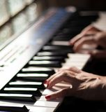 Playing beautiful music with a keyboard. A beautiful scene of a woman playing music with a beautiful casio keyboard royalty free stock photos