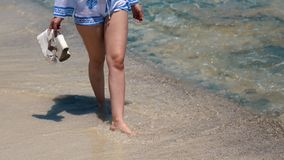 Beautiful scene of a woman walking on ocean beach. Young barefoot girl along the surf line.  stock photos