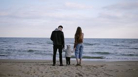 Beautiful scene of young, fashioned couple with their child standing in front the sea and looking on horizon. Windy stock video footage