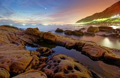 Beautiful scenery of dawning sky by rocky beach in northern Taiwan Stock Image
