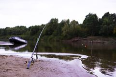 Beautiful scenery of fishing concept. fish rod on the sandy river bank at the dusk d royalty free stock photography
