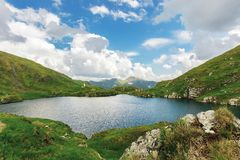 Beautiful scenery on the glacier lake capra. Gorgeous cloudscape above the distant fagaras mountain ridge. steep grassy slopes with rocky formations. dramatic stock photography