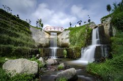 Beautiful scenery of hidden waterfall with cloudy sky. In the middle of tea farm at Cameron Highland, Malaysia.Soft focus and some motion blur due to long stock images