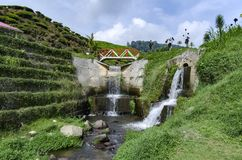 Beautiful scenery of hidden waterfall with cloudy sky. In the middle of tea farm at Cameron Highland, Malaysia.Soft focus and some motion blur due to long stock image