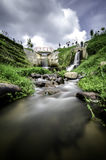 Beautiful scenery of hidden waterfall with cloudy sky in the middle of tea farm at Cameron Highland, Malaysia. Soft focus and some motion blur due to long royalty free stock images