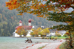 Beautiful scenery of Lake Konigssee with famous Sankt Bartholomae pilgrimage church by the lakeside and autumn mountains in foggy Stock Image
