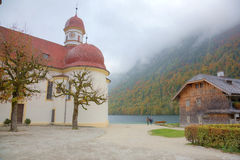 Beautiful scenery of Lake Konigssee with famous Sankt Bartholomae pilgrimage church by the lakeside and autumn mountains in foggy Stock Photos