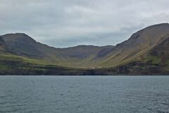 Beautiful scenery of Mulafossur Waterfall Goose valley and Gasadalur village view from water. Vagar island Faroe is