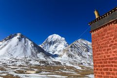 Beautiful North face of sacred Kailash mountain with old red brick building in foreground. Beautiful scenery North face of sacred Kailash mountain covered with Royalty Free Stock Photos