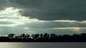 Beautiful scenery rays sun shine through clouds over summer river. Panoramic view river on a summer day stock video