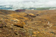Beautiful scenery slopes of volcano Mutnovsky with clouds. Royalty Free Stock Photos