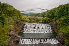 Beautiful scenery of small dam with waterfalls in early autumn season at Yamabikotsuri Bridge. Royalty Free Stock Photos