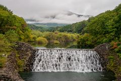 Beautiful scenery of small dam with waterfalls in early autumn season at Yamabikotsuri Bridge. Stock Images