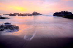 Beautiful scenery of sunrise by the rocky seashore Royalty Free Stock Photos