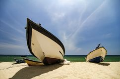traditional fisherman boat moored over beautiful sea view and sandy beach under bright sunny day Stock Photo