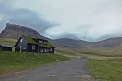 Beautiful scenery with typical house with grass roof Gasadalur village Goose valley. Faroe Islands