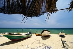 Traditional fisherman boat stranded on deserted sandy beach under bright sunny day. Beautiful scenery under bamboo hut, traditional fisherman boat stranded on Stock Photography