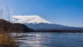 Beautiful scenery View of Mount Fuji at kawaguchiko, Japan in the sunny day with moving cloud. Lake kawaguchi is a very popular for tourists and photographers stock footage