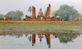 Beautiful scenery of Wat Mahathat Temple in Sukhothai Historical Park, Thailand, with view of a Buddha statue seated Stock Photo