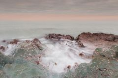 A beautiful scenery of wave splashing at the sunrise. A little noise grainy texture stock image