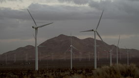 The beautiful scenery of windmills with massive mountains on the background stock footage