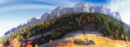 Beautiful scenic golden autumn landscape of majestic Bolshoy Tkhach rocky mountain peak under blue sky at sunrise with wooden tour. Ist hut on foreground royalty free stock photos