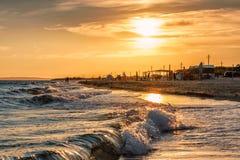 Scenic landscape of sandy beach at Anapa resort on Black Sea coast with surfing waves and people on seashore. Summer sunset seasid stock image
