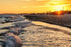Scenic landscape of sandy beach at Anapa resort on Black Sea coast with surfing waves and people on seashore. Summer sunset seasid royalty free stock photos