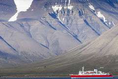 Beautiful scenic view with norge cruise boat docked at Longyearbyen port against the background of fogged black mountain and calm royalty free stock image