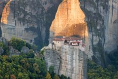 Beautiful scenic view, Orthodox Monastery of Rousanou St. Barbara, immense monolithic pillar, green and yellow foliage Royalty Free Stock Images
