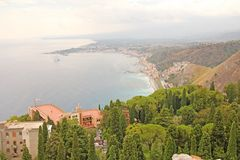 Beautiful Scenic View of the Sea, Green Forest, Taormina`s Old Town and Etna Volcano. The island of Sicily, Italy royalty free stock photography