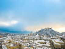 Beautiful scenic winter landscape in historic city of Salzburg with snowy rooftops, cathedrals and famous fortress Hohensalzburg b. Lue sky space Stock Photo
