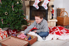 Beautiful school boy decorating  Christmas tree Royalty Free Stock Photo