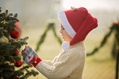 Beautiful school child, boy, decorating Christmas tree on a fros Royalty Free Stock Photos