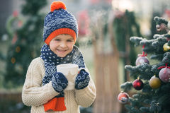 Beautiful school child, boy, holding Christmas mug, drinking tea Royalty Free Stock Images