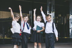 Beautiful school children active and happy on the background of. School in uniform Royalty Free Stock Images