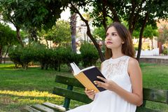 Beautiful school or college girl is sitting on the bench with a book in the hands and thinking about something in the park stock photography