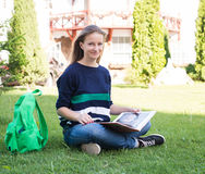 Beautiful school or college girl sitting on the grass with books and bag studying in a park. Stock Photos