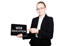 Beautiful school girl in a business suit holds a pc tablet in his hands and looking into the camera, on a pc tablet Royalty Free Stock Images