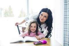 Beautiful school girl doing homework with mother at home Royalty Free Stock Images