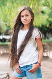 Beautiful school girl with long hair in the park.  Prety Girl wi. Th a model appearance and with fashionable poses. Child of 8 years Royalty Free Stock Photos