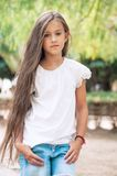 Beautiful school girl with long hair in the park.  Prety Girl wi. Th a model appearance and with fashionable poses. Child of 8 years Stock Photo