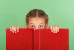 Beautiful school girl peeping from behind her red book. Isolated on green royalty free stock photos