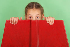 Beautiful school girl peeping from behind her red book. Isolated on green stock image