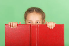 Beautiful school girl peeping from behind her red book. Isolated on green royalty free stock image