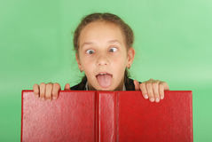 Beautiful school girl peeping from behind her red book. Pull a face. Isolated on green royalty free stock image