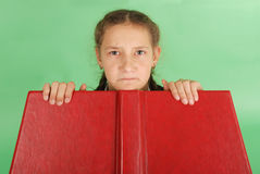 Beautiful school girl peeping from behind her red book. Pull a face. Isolated on green stock image