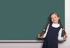 Beautiful school girl with pigtail smiled near blank chalkboard background, dressed in classic black suit, education concept Royalty Free Stock Image